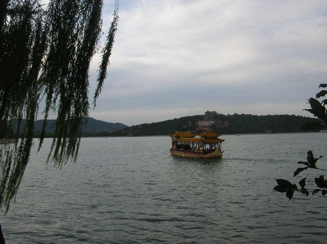 Китайская прогулочная лодка на озере в Императорском парке Ихэюань г. Пекин