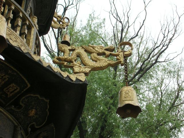 Драконы с колокольчиками, отгоняющими злых духов, на крыше пагоды в буддийском храме города Харбин