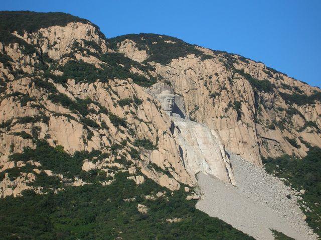 Каменное изображение Будды на скале в парке Долголетия