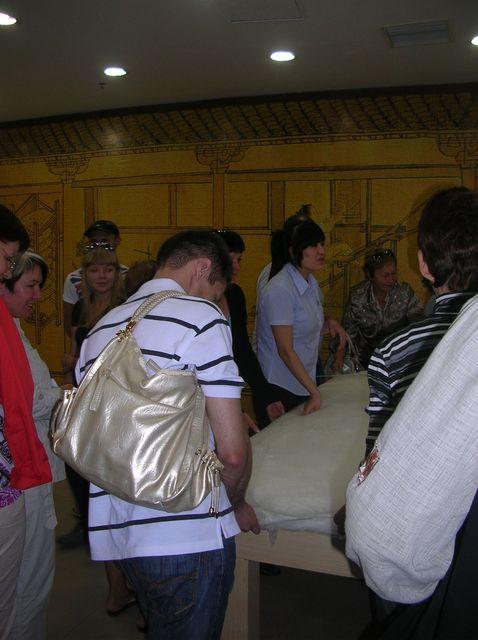 Довольные туристы принимают участие в изготовлении шёлкового одеяла