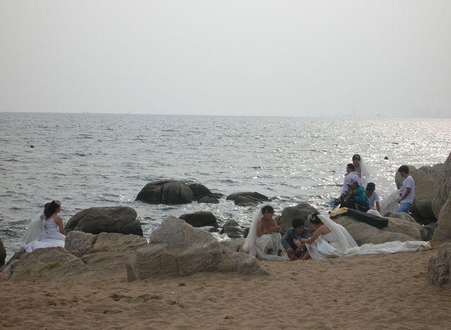 Уставшие женихи и невесты после фотосессии на морском побережье Циньхуандао