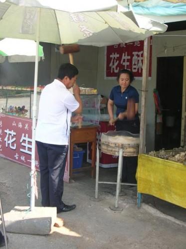 Изготовление национальных сладостей на улице в Бэйдайхэ